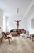 Brown and white interior with life-size crucifix above leather sofa; fifties-style designer chair with cowhide cover