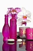 Hot pink bottles decorated with sprigs of orchids and tea light holders