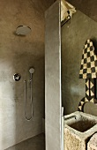 Grey, spatula-effect walls in designer bathroom with open shower area and stone trough as sink; ethnic artwork reflected in mirror