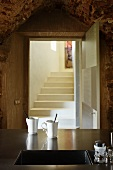 Two coffee mugs next to undermount sink in stainless steel worksurface; view of masonry steps through open door in background