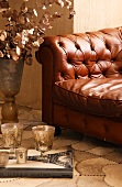 Glasses on book in front of brown quilted leather sofa with buttons; floor covering with curving, segmented pattern