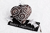 Heart-shaped Christmas tree decoration lying on little card
