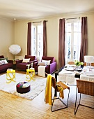 Set dining table next to lounge area with yellow side tables and purple sofa set in front of French windows with floor-length curtains