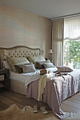 Clothing on double bed with curved headboard next to large window with view of garden