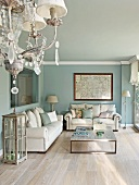 Chandelier and lounge area with white sofa set and modern coffee table against walls painted pale blue in traditional setting