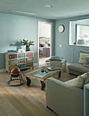 Rustic coffee table on castors in lounge area with walls painted pale blue and view through open bedroom door