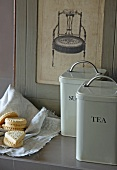 Vintage storage cans with labels next to biscuits on cloth