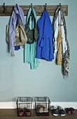 Open-plan cloakroom - clothing on vintage rack of wall hooks and wire baskets of shoes against wall painted pale blue