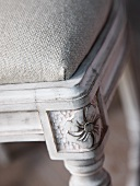 Detail of wooden chair frame with carved feet and cushion with linen upholstery