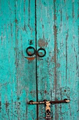 Weathered wooden door with peeling, pale blue paint