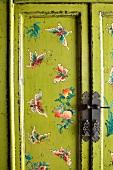 Vintage Kleiderschrank mit Schmetterlingmotiven auf gelb-grünem Untergrund