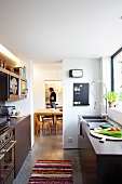 Designer fitted kitchen with smooth, dark doors and professional pull out spray tap; view into adjoining dining room with man in background