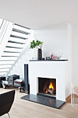 Fire in modern fireplace with dark stone hearth and mantelpiece next to hifi system on trolley under airy staircase