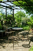 Sunny terrace and garden - delicate, metal, rust-effect table and chairs and wooden bench on stone-flagged terrace with climber-covered wooden pergola