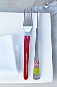 Designer cutlery decorated with patterned tape on square plate