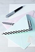 Schwarzweiss gemustertes Masking Tape auf Briefumschlägen, Kugelschreiber im Hintergrund