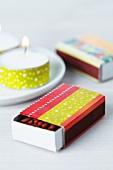 Mit rotem und gelbem Master Tape beklebte Streichholzschachtel und mit gelbem Tape verziertes Teelicht