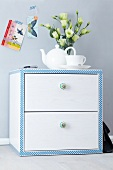 Small chest of drawers decorated with patterned tape with vase of Texas bluebells and romantic postcards on wall