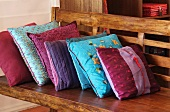 Cushions with variously patterned silk covers on wooden bench