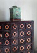 Asiatischer Porzellanbehälter mit Deckel auf bemalter Holzkommode