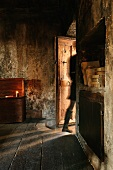 Figure moving through half-open door of old room with sooty walls