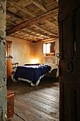 View of bed in rustic bedroom with wooden coffered ceiling through open door