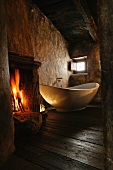Atmospheric old room with open fire next to free-standing designer bathtub