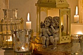 Angel figurines sitting in lantern and tea light holders with lit candles