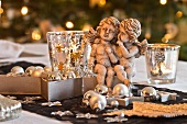Pair of angels and Christmas decorations next to glass tea light holders