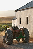 Tractor next to simple farmhouse