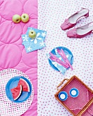 A picnic basket, fruit, napkins and shoes on a rug