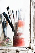 Used paint brushes in jars on the window sill