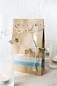 Papiertüte verziert mit Masking Tape und weisser Kordel zwischen Gläsern und Kerzen