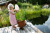 Blonde girl watering potted plant next to garden pond