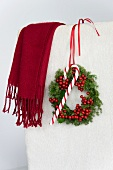Christmas wreath of holly berries and conifer hanging on chair back with candy cane