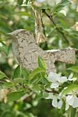 Wooden bird figurine on twig