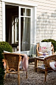 Group of wicker chairs and coffee service on small table in front of terrace doors of wooden house
