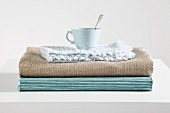 Tea cup on stack of table runners