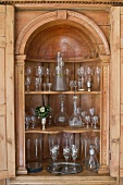 Glass collection in ornately carved cabinet with rounded arch