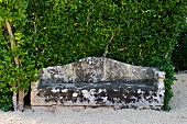 Weathered stone bench on gravel in garden