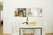 White, modern dining area with red wine and bread on table in front of service hatch to kitchen