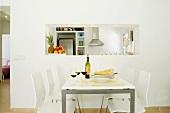 Moderner Essplatz in Weiss mit Rotwein und Brot gedeckt vor Küchendurchreiche