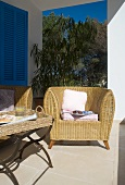 Comfortable wicker armchair and side table on Mediterranean veranda