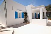 Mediterranean apartment block architecture with blue shutters below a sunny sky