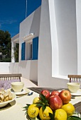 Breakfast table with fresh fruit on Mediterranean terrace of apartment building