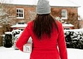 Frau geht mit Geschenkpaket zum verschneiten Haus
