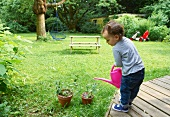 Toddler boy watering plants in backyard