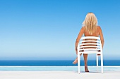 Woman relaxing in plastic chair by the sea