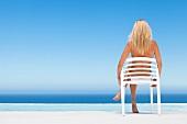 Blonde Frau sitzt im Plastikstuhl am Meer