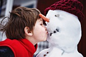 Close up of boy kissing snowman